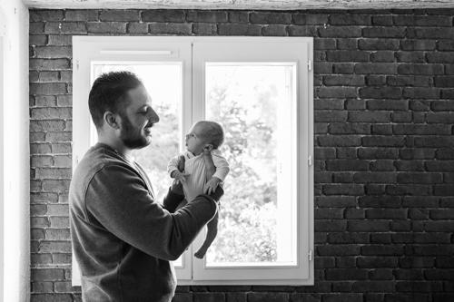 un papa pose devant une fenêtre lors dune séance photo naissance à son domicile à Nice. Photo prise par Myriam Ohayon Photographe.