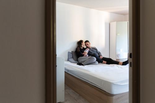 Un couple pose sur son lit avec son bébé lors d'une séance photo à Nice . Photo prise par Myriam Ohayon Photographe