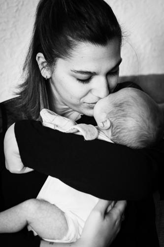 Photo en noir et blanc d'une maman embrassant son bébé. Photo prise lors d'une séance naissance à Nice . Myriam Ohayon Photographe