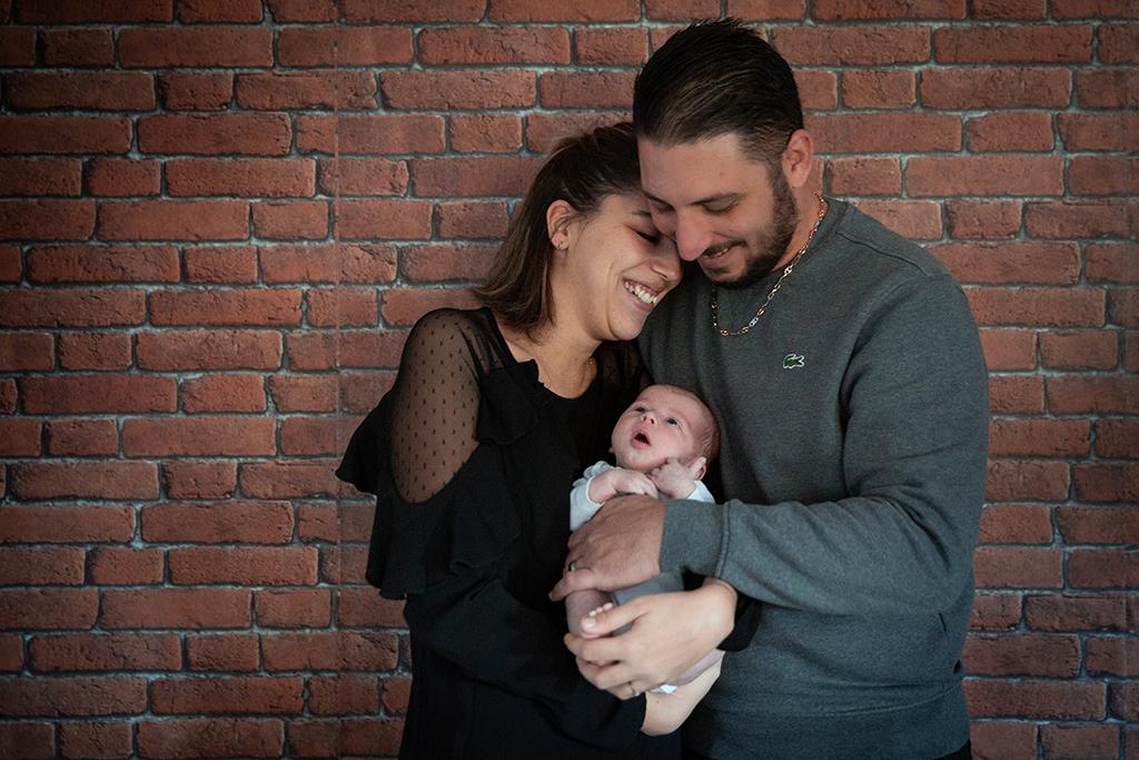 Un couple pose avec son bébé lors d'une séance photo naissance à domicile à Nice. Photo prise par Myriam Ohayon Photographe