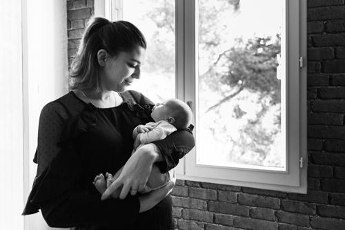 une maman porte tendrement son fils dans ses bras. Il pose devant une fenêtre lors dune séance photo naissance à son domicile à Nice. Photo prise par Myriam Ohayon Photographe.