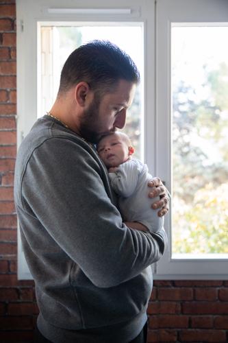 un papa porte tendrement son fils dans ses bras. Il pose devant une fenêtre lors dune séance photo naissance à son domicile à Nice. Photo prise par Myriam Ohayon Photographe.