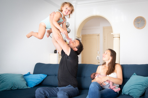 Un papa s'amuse avec sa fille pendant que la maman allaite leur bébé. Photo prise par Myriam Ohayon Photographe à Nice