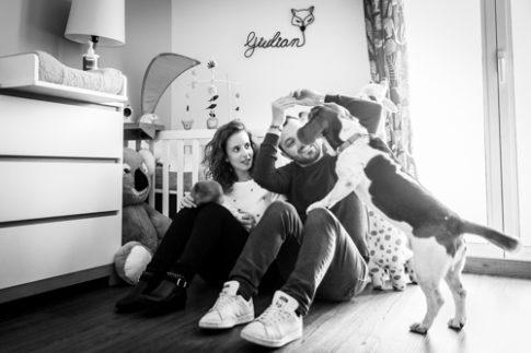 Un couple pose avec leur bébé et leur chien lors d'une séance photo naissance à domicile. Photo prise par Myriam Ohayon Photographe à Pégomas