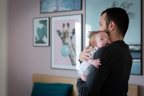 Un papa porte son nouveau-né dans les bras lors d'une séance photo naissance. Photo prise par Myriam Ohayon Photographe à Pégomas