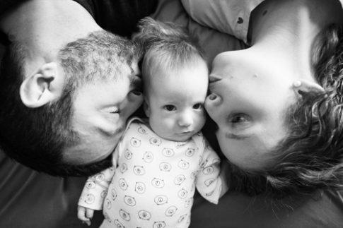 Photo en noir et blanc. Gros plan sur le visage d'un couple embrassant son bébé. Photo prise par Myriam Ohayon Photographe à Pégomas