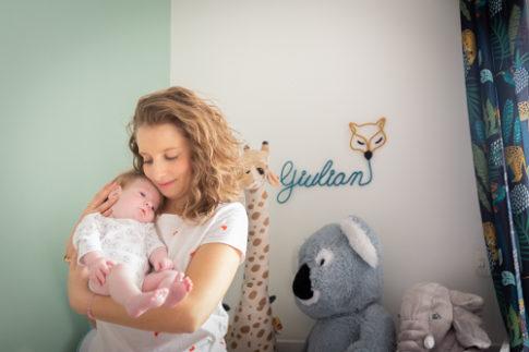 Une maman porte son nouveau-né dans les bras lors d'une séance photo naissance. Photo prise par Myriam Ohayon Photographe à Pégomas
