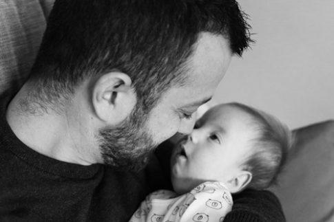 Photo en noir et blanc d'un papa embrassant son bébé lors d'une séance photo naissance à Pégomas. Photo prise par Myriam Ohayon Photographe