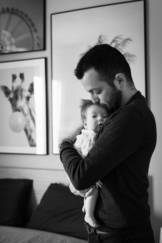 un papa porte tendrement son fils dans ses bras. Il pose lors d'une séance photo naissance à son domicile à Pégomas. Photo en noir et blanc prise par Myriam Ohayon Photographe.