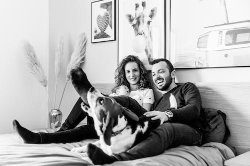 photo en noir et blanc d'un couple posant avec leur bébé sur leur lit pendant que leur chien beagle mange la chaussette du papa. Photo prise par Myriam Ohayon Photographe à Pégomas