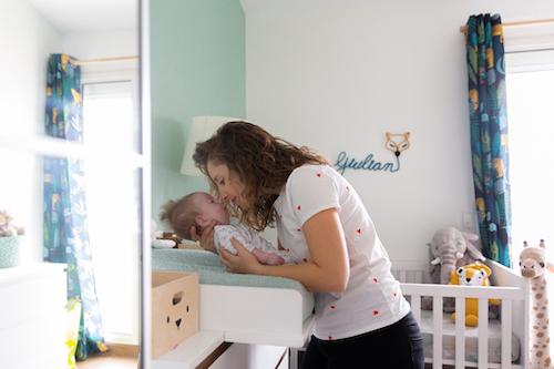 une maman embrasse son fils sur la table à langer lors d'un reportage photo lifestyle pour la naissance de son fils.
