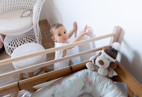Une petite fille d'un an joue avec un interrupteur dans sa chambre. lors d'une séance Smash the cake à Pégomas. Photo prise par Myriam Ohayon Photographe
