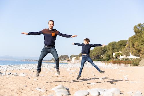 Un garçon de 7 ans et son papa s'amusent à sauter sur la plage de Saint-Raphaël.