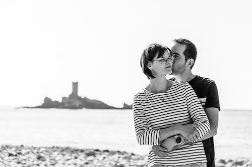 Photo en noir et blanc d'un couple sur la plage. Monsieur embrasse Madame dans le cou.