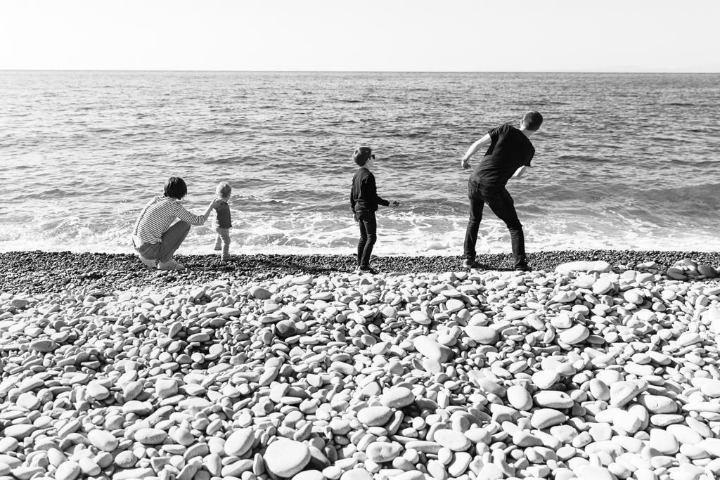 Une famille s'amuse à jeter des cailloux dans l'eau. Photo prise de dos par Myriam Ohayon Photographe à Saint-Raphaël