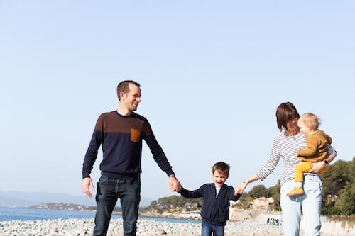 Un papa et une maman se promènent sur la plage de Saint-Raphaël avec leurs deux garçons lors d'une séance photo.