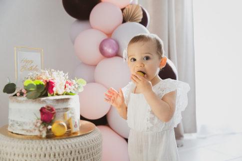 Une petite fille déguste un macaron lors d'une séance Smash the cake à Pégomas. Photo prise par Myriam Ohayon Photographe