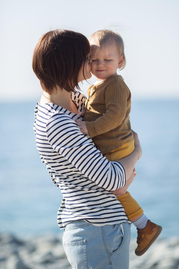 Une maman porte et embrasse son petit garçon de deux ans lors d'une séance photo en famille sur la plage de Saint-Raphaël.