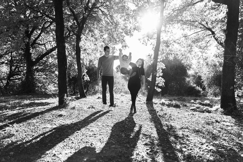 Un couple s'amuse dans un parc avec leur enfant. La femme est enceinte. Photo prise lors d'une séance grossesse à Nice.