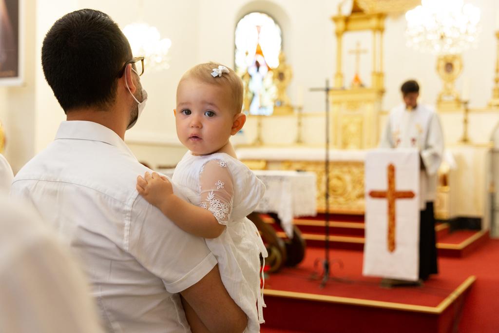 une petite fille dans les bras de son papa regarde la photographe durant son baptême. Photo prise par Myriam Ohayon Photographe à Nice