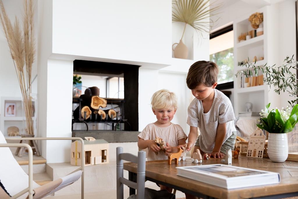 deux frères jouent avec des petites figurines en bois. Photo prise par Myriam Ohayon Photographe lors d'un reportage lifestyle en famille à domicile